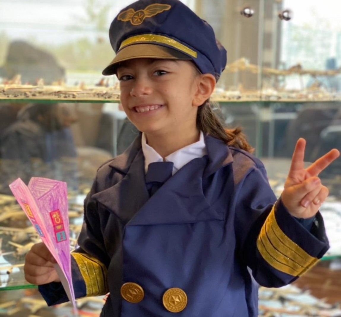 Girl in pilot uniform with pink paper plane